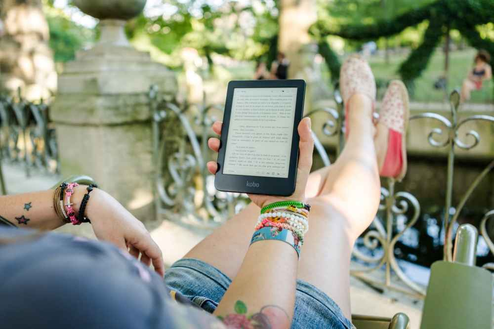 person holding person holding kobo e reader