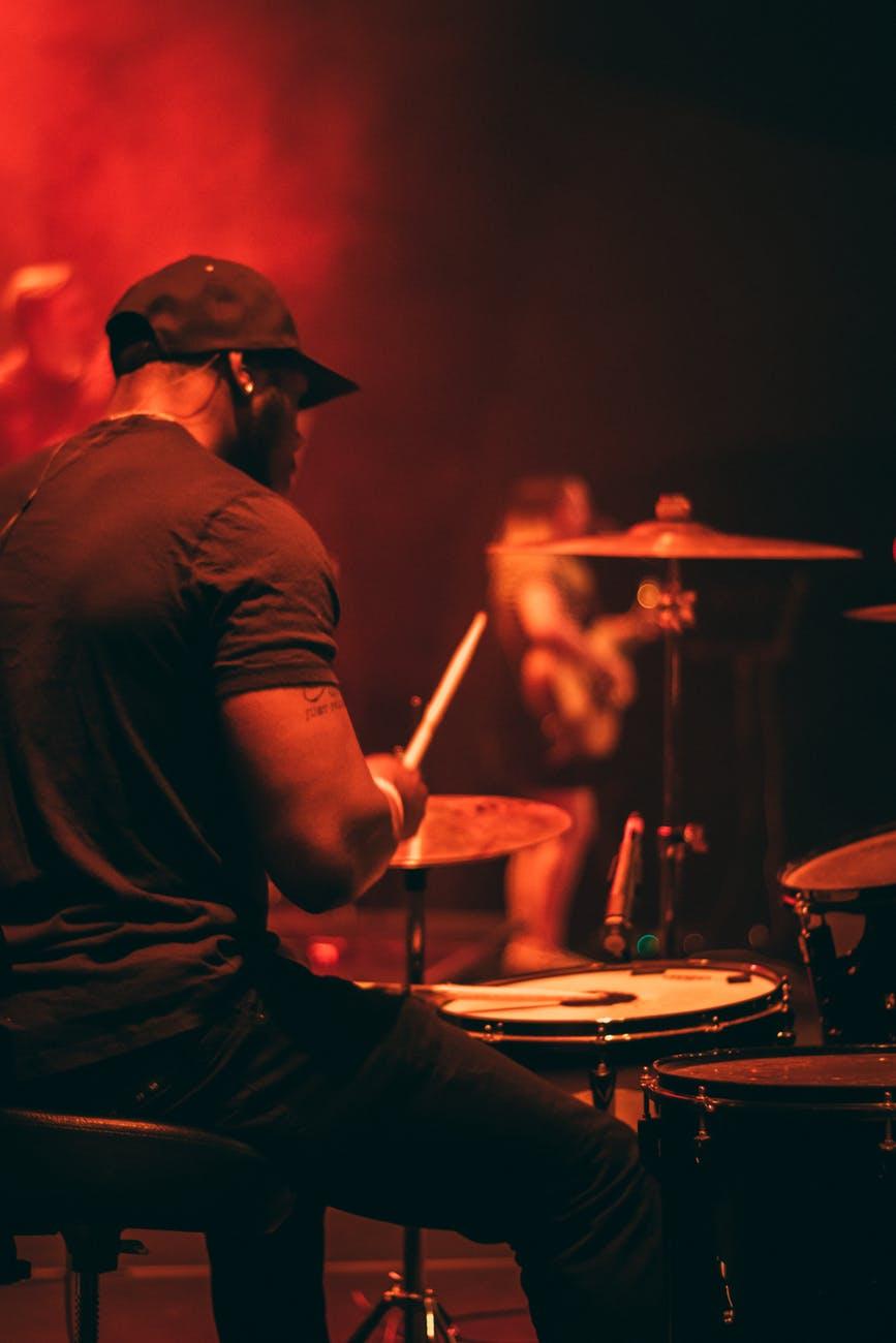 man s wearing black shirt playing drum